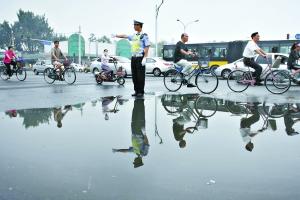 8月7日,因为大雨,和平门路口出现积水。为了方便来往的行人过马路,孟昆玉特意站在积水边缘指挥车辆从前面绕行。